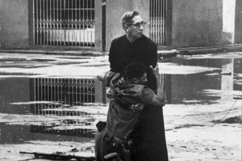 A priest comforts a dying soldier, 1962.