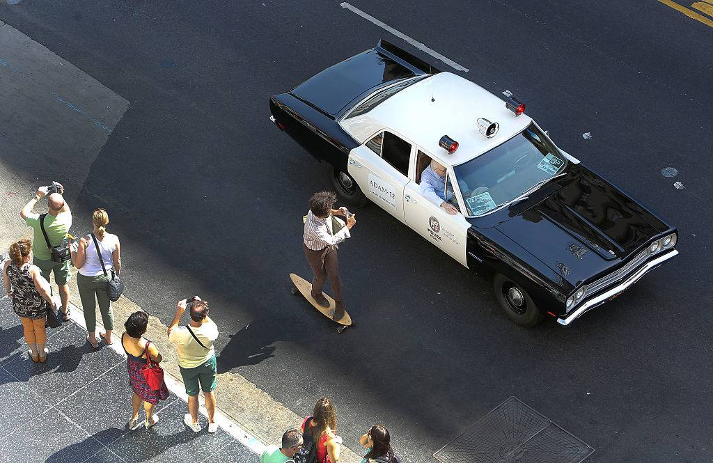 A skateboarder photographs a 1972 AMC Matador vehicle