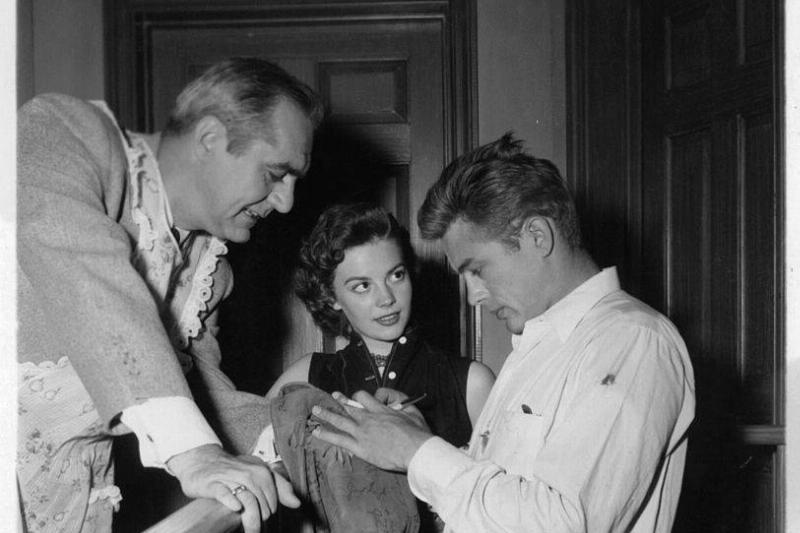 Jim Backus and Natalie Wood watch as James Dean autographs a jacket during a break from shooting the film 'Rebel Without A Cause'