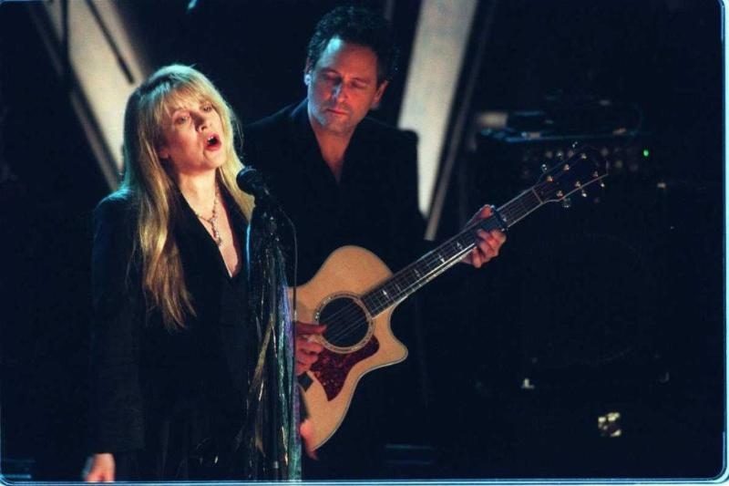 Stevie Nicks sings while bandmate Lindsey Buckingham looks on during a performance by Fleetwood Mac as the band is inducted into Rock & Roll's Hall of Fame
