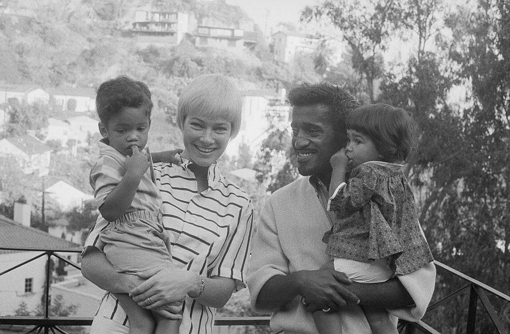 Versatile entertainer Sammy Davis, Jr., and his wife, actress May Britt, pose with their newly enlarged family in the garden of their home November 10th