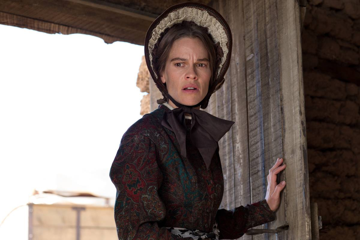 hilary swank wearing a bonnet in the homesman