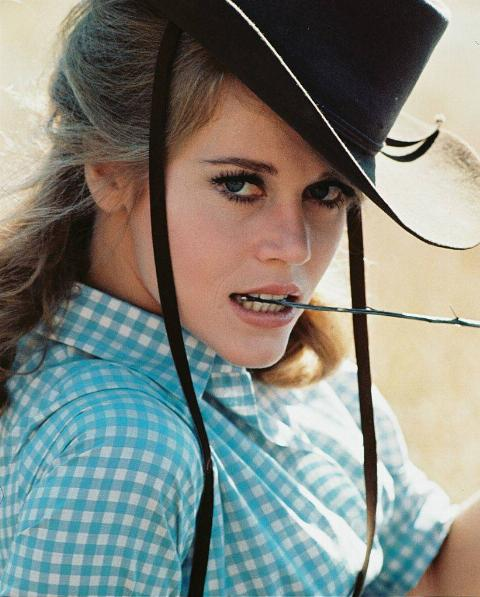 jane fonda wearing a cowboy hat and holding a stick in her mouth