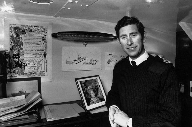 1976: Charles, Prince of Wales as a Lieutenant in the Royal Navy, poses beside a photograph of his Queen Elizabeth the Queen Mother in his cabin aboard HMS Bronington.