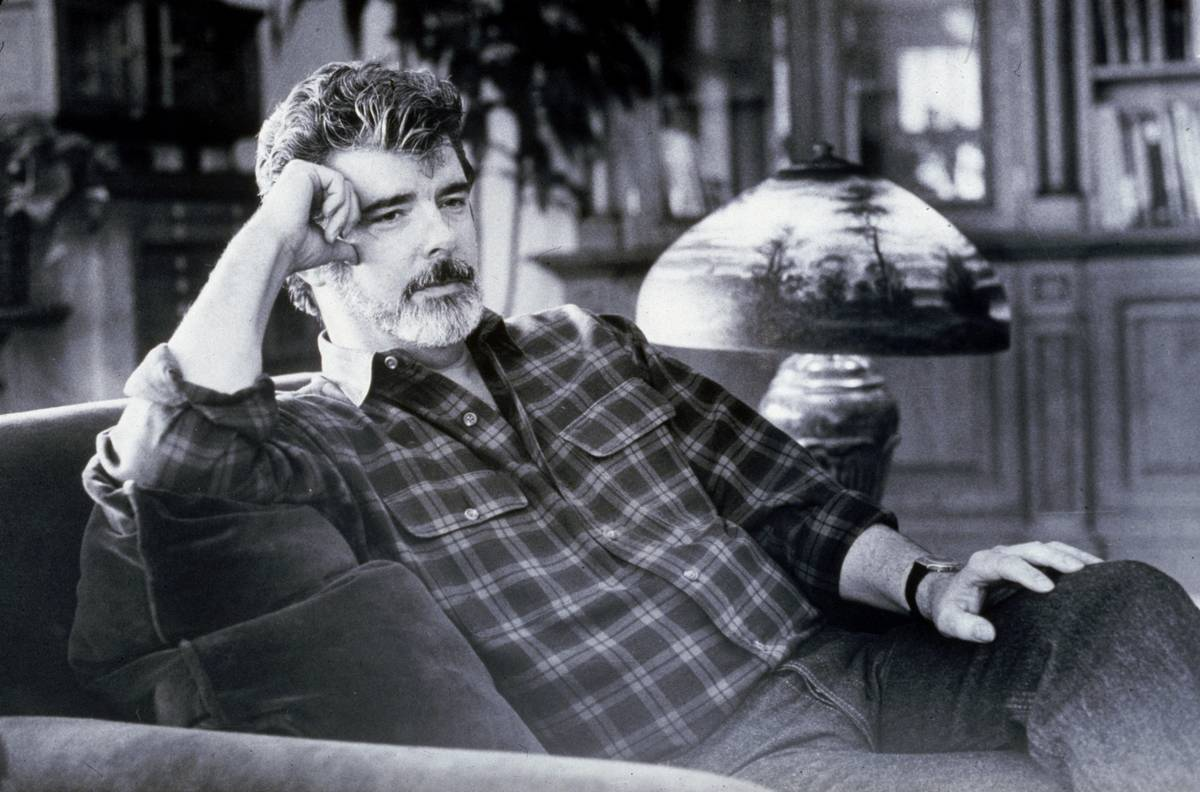 George Lucas lounges in a chair.
