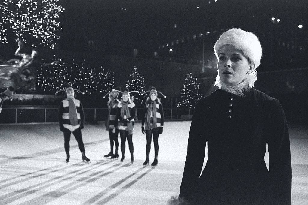 Actress Candice Bergen, wearing a Santa's helper costume, skates near the Saturday Night Live Bumble Bees for a skit