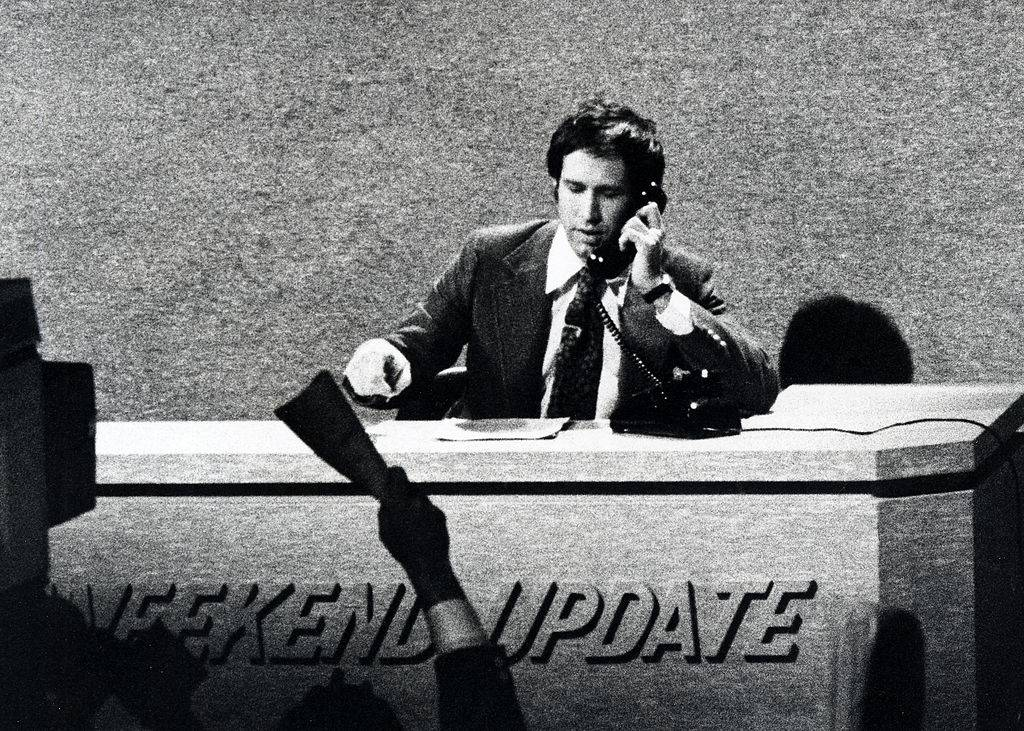 chevy chase talking on the phone at his weekend update desk