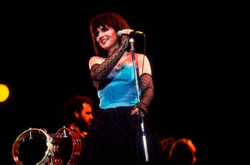 Linda Ronstadt wearing a blue top and fingerless gloves