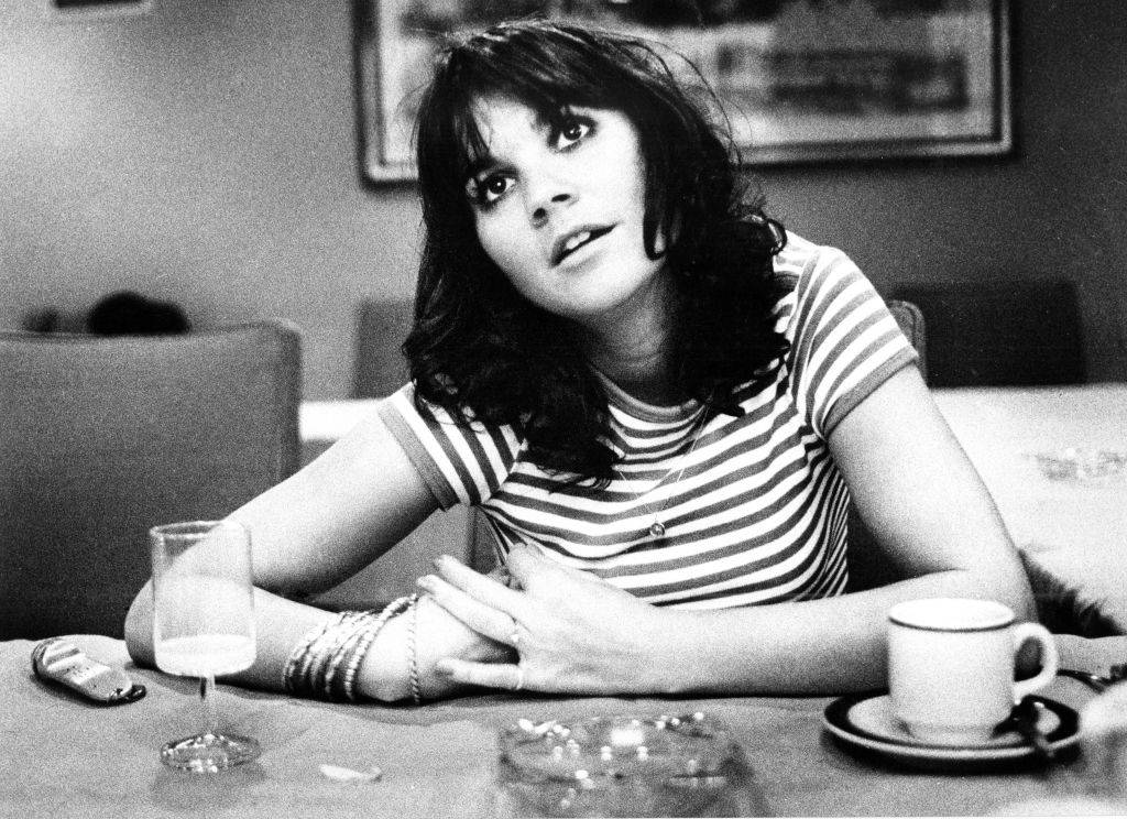 Linda Ronstadt wearing a striped shirt and drinking