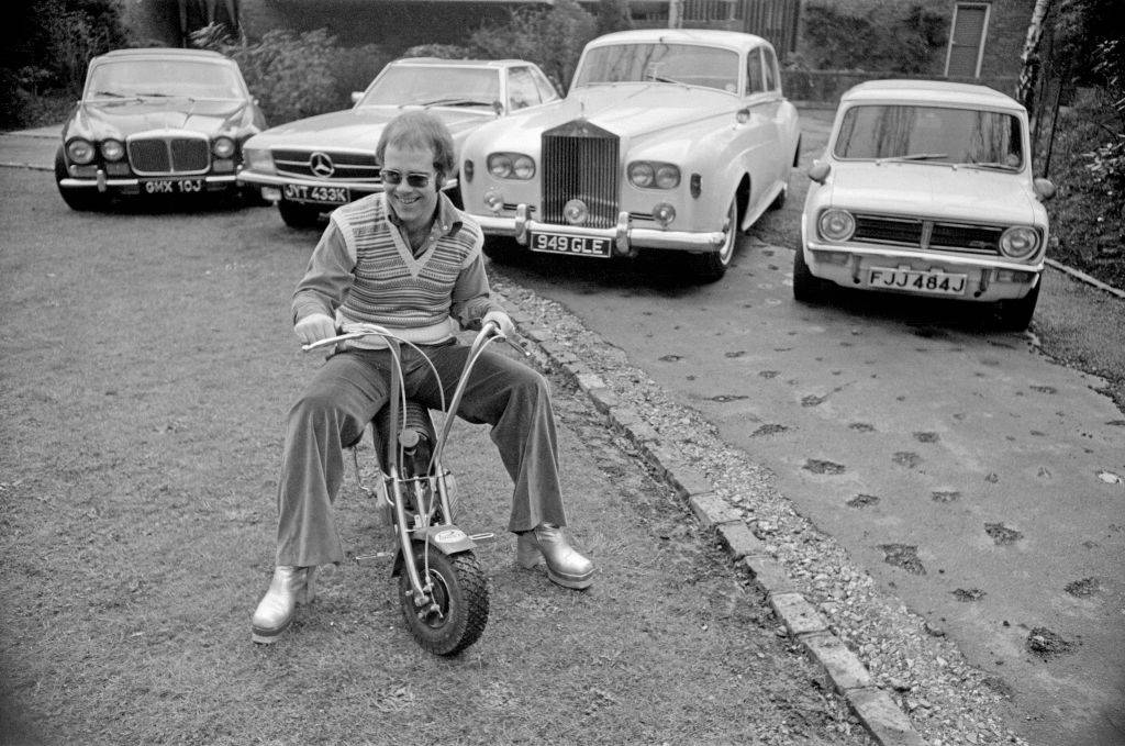 elton john riding a motorbike in front of his fancy cars