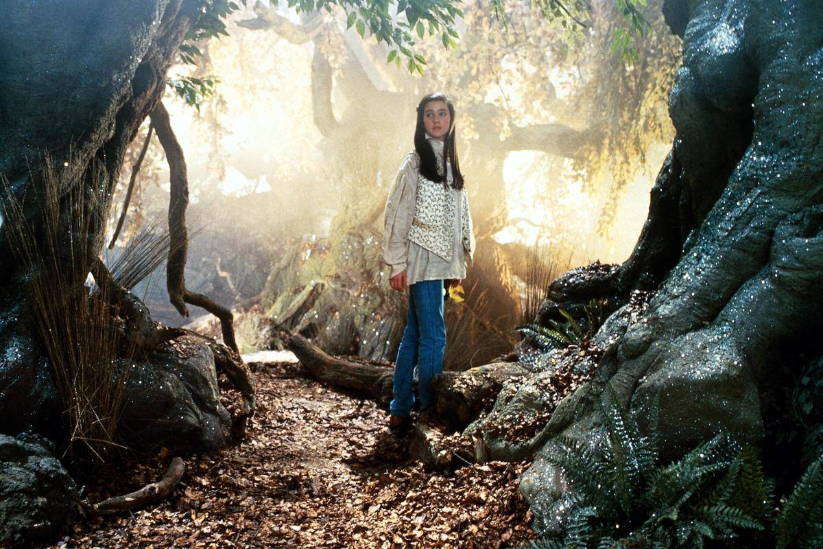 Jennifer Connelly stands in a forest in this Labyrinth publicity still.