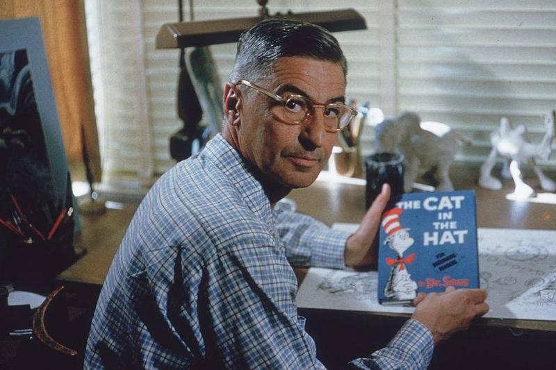 Dr. Seuss holding a copy of The Cat in the Hat at his drafting table