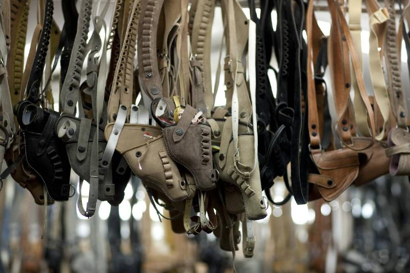 Holsters for sale hang from a rail.