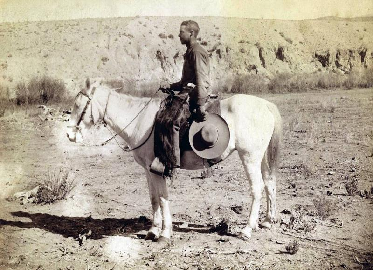 A southwestern cowboy sits on a horse in 1878.