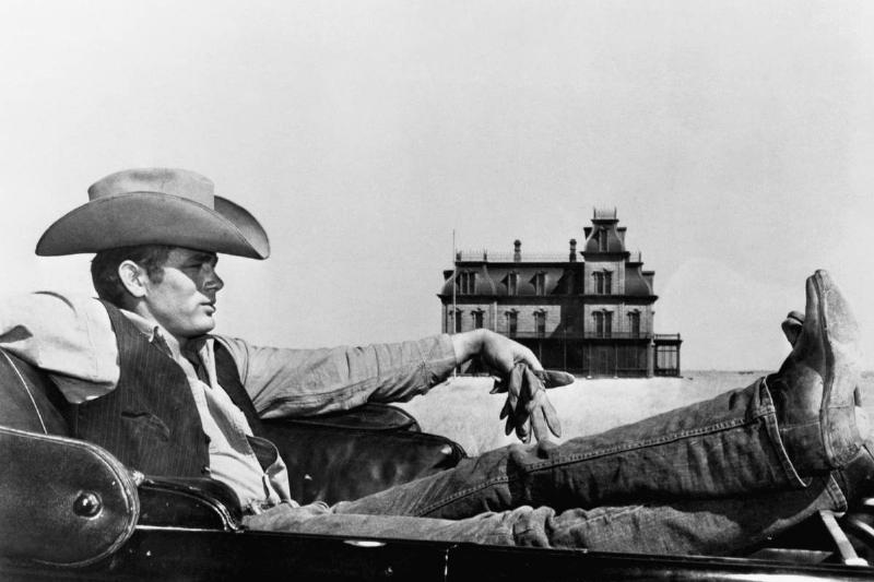 American actor James Dean poses for a movie wearing a cowboy hat.