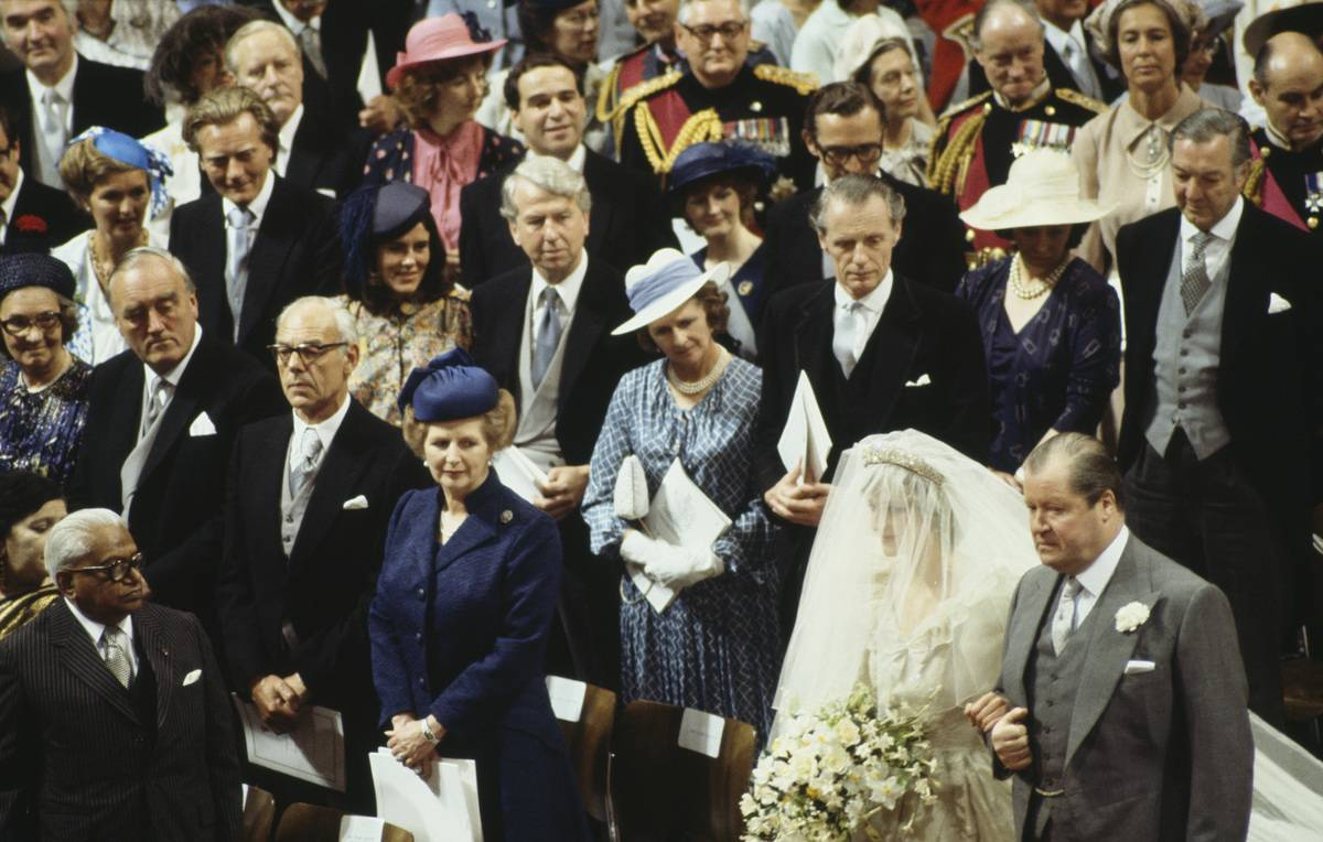Lady Diana and her father walk down the aisle as onlookers watch her.