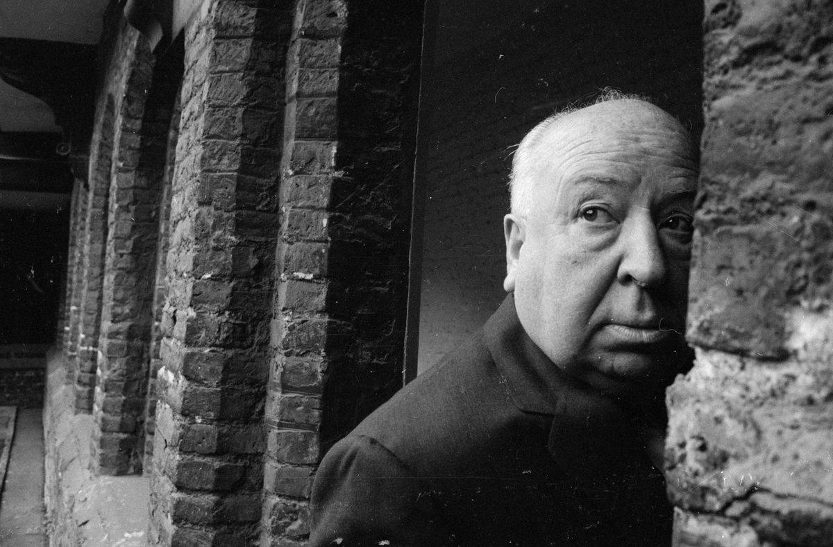 Alfred Hitchcock wanders through the arches in Cambridge, 1966.