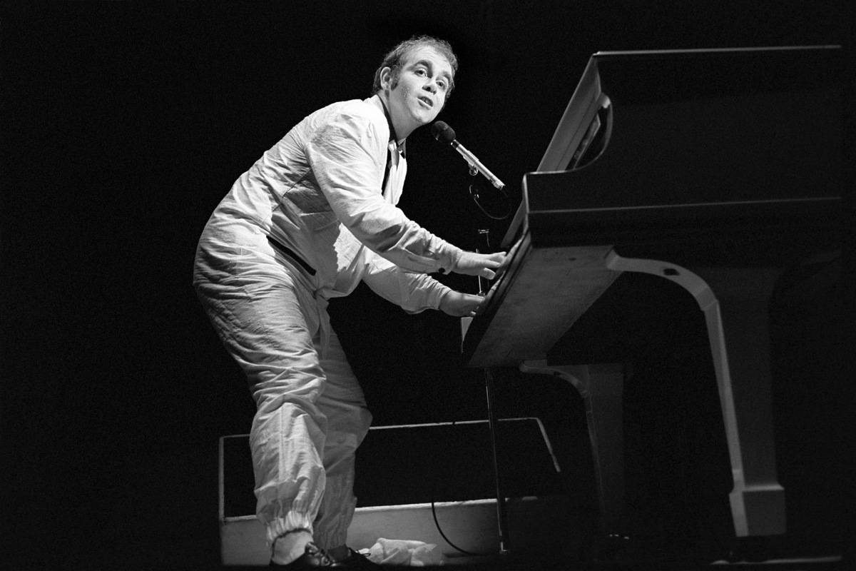 Elton John sings and plays the piano onstage, 1979.