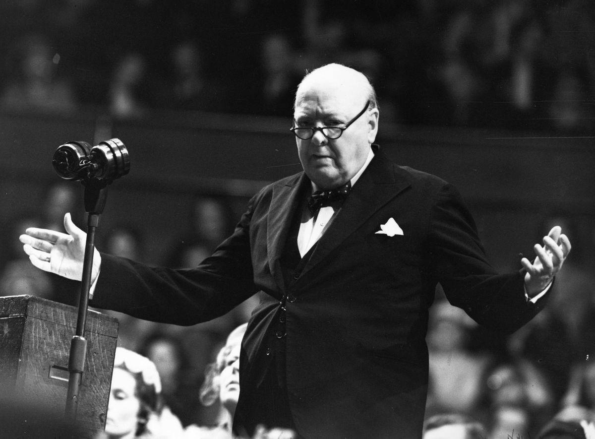 A 1954 photograph shows Sir Winston Churchill addressing a crowd at a microphone.