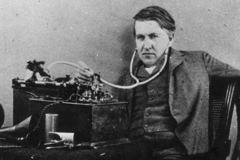 Thomas Edison listens to his machine through a stethoscope in his ears.