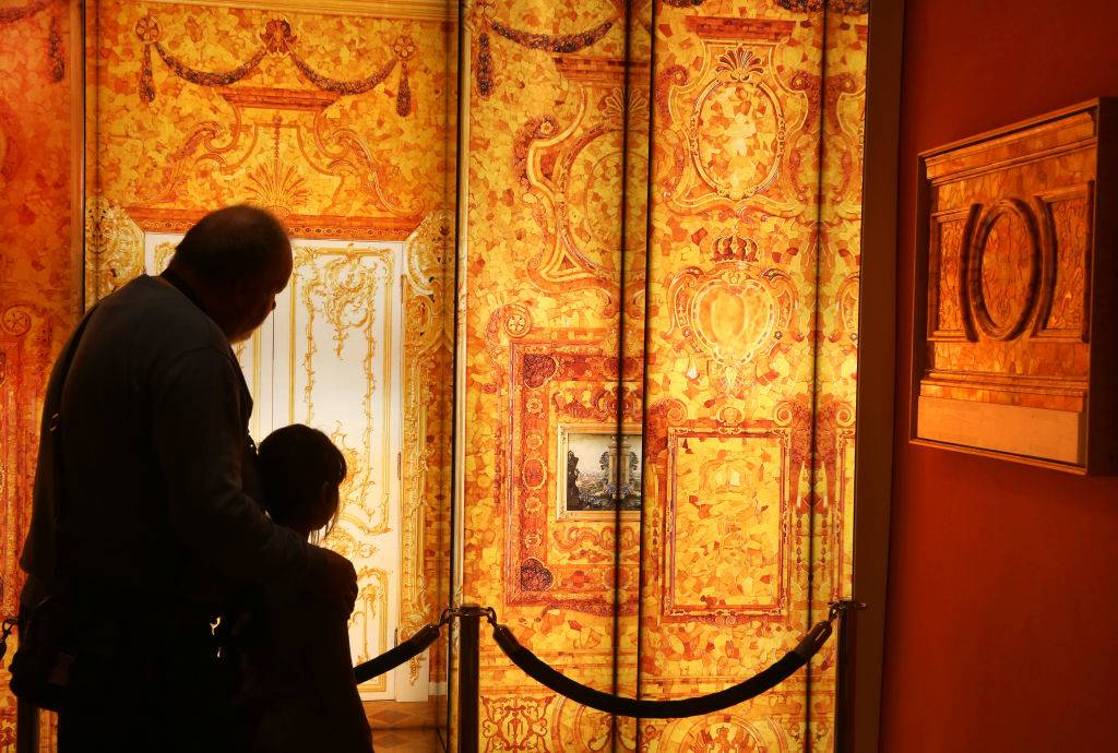 Visitors walk past images of the missing Amber Room