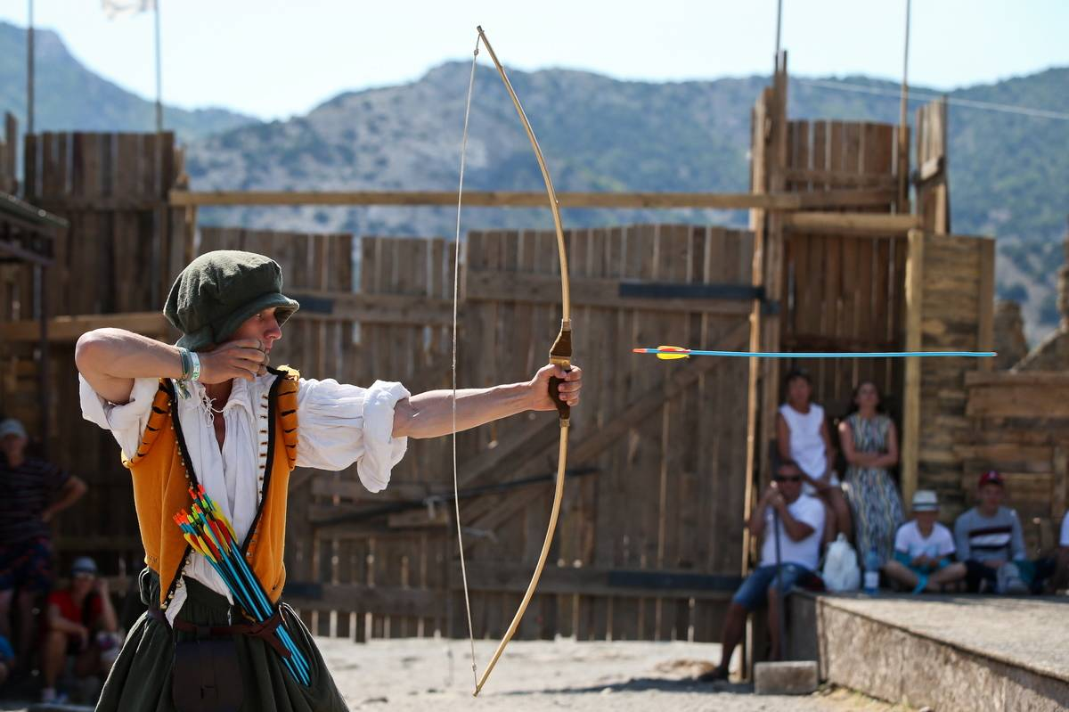 People participate in an archery contest during a medieval fair.