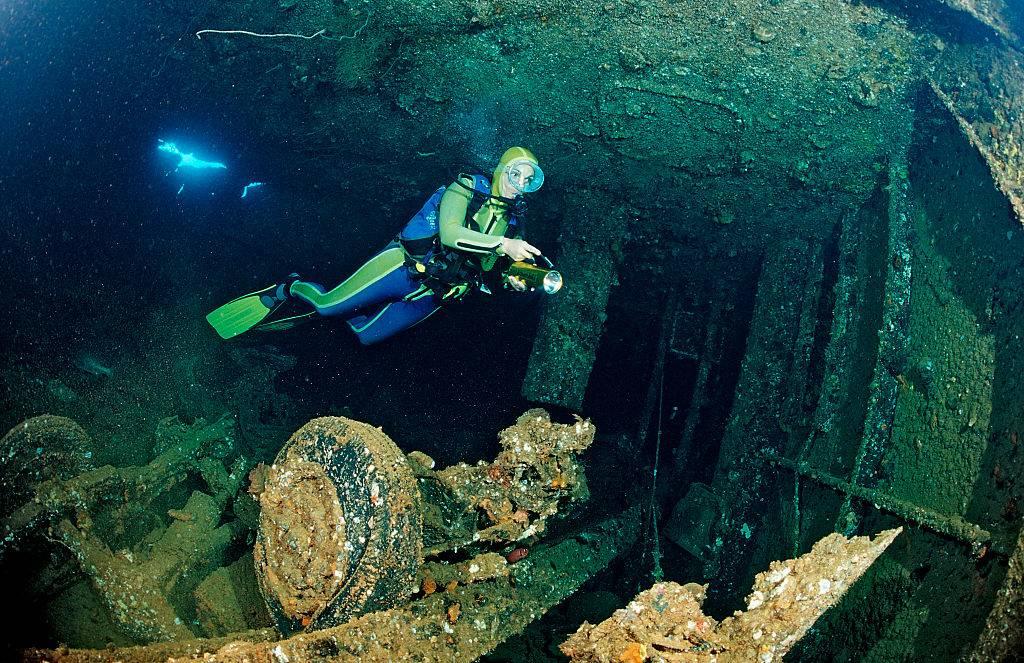 a scuba diver looking at a shipwreck