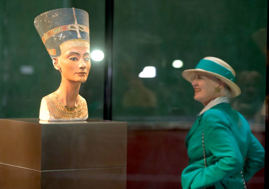 Queen Margrethe II of Denmark looks at the bust of Nefertiti