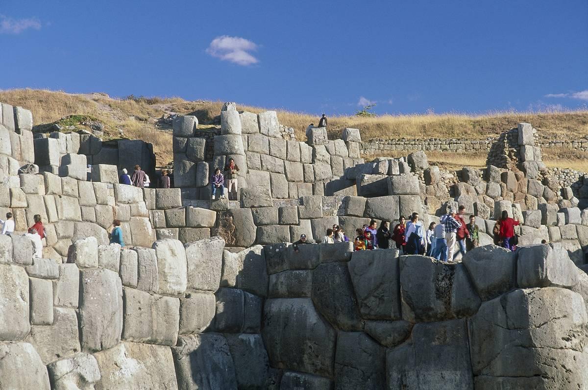 Tourists walk around the ruins of Sacsayhuamán, Peru.