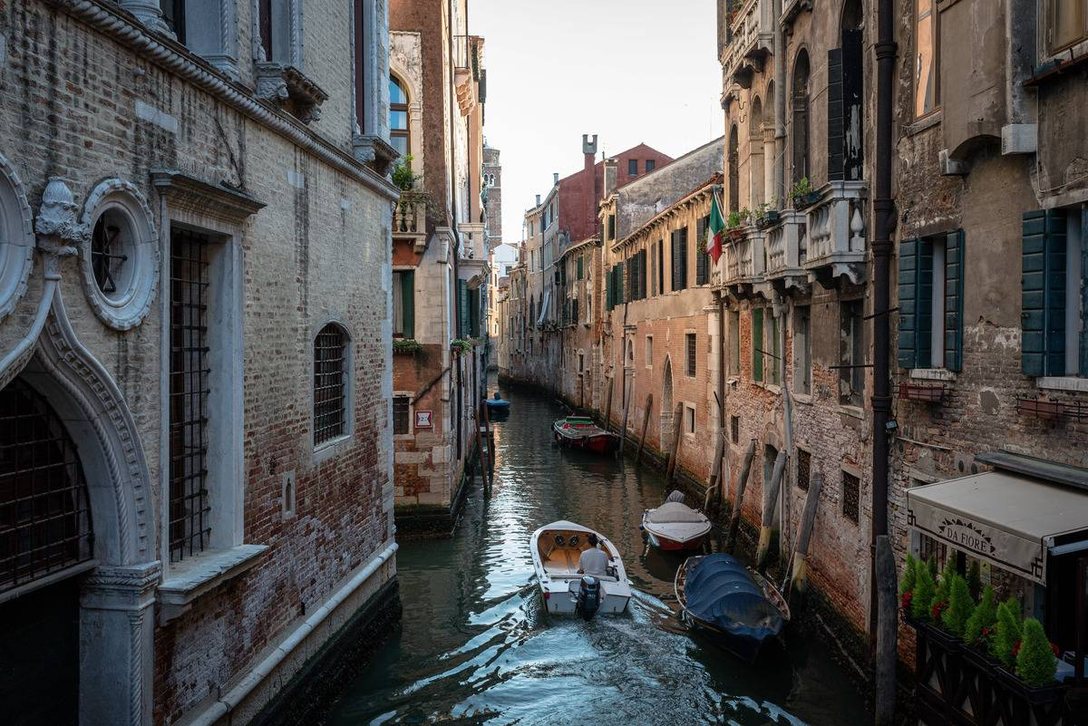 A boat drives through a canal in Venice.