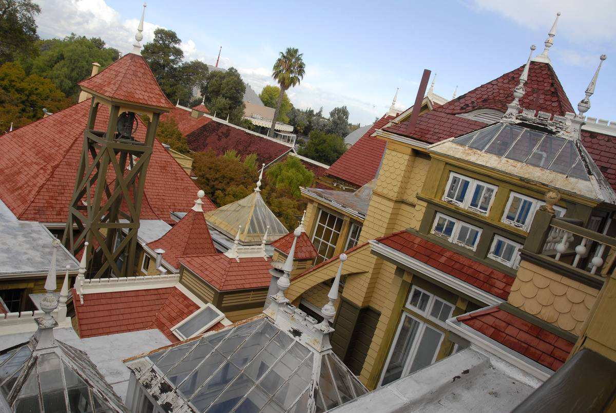 A photo shows the roofs of the Winchester Mystery House.