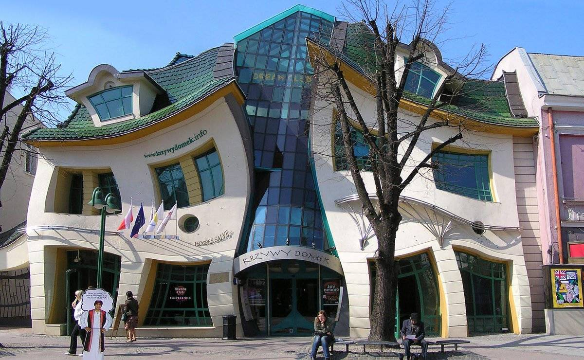 Tourists stand in front of the Crooked House in Poland.