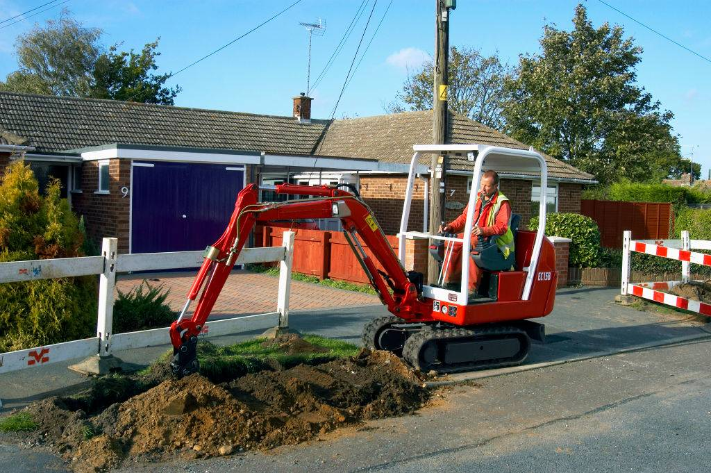 Utility company excavating the pavement with mini digger