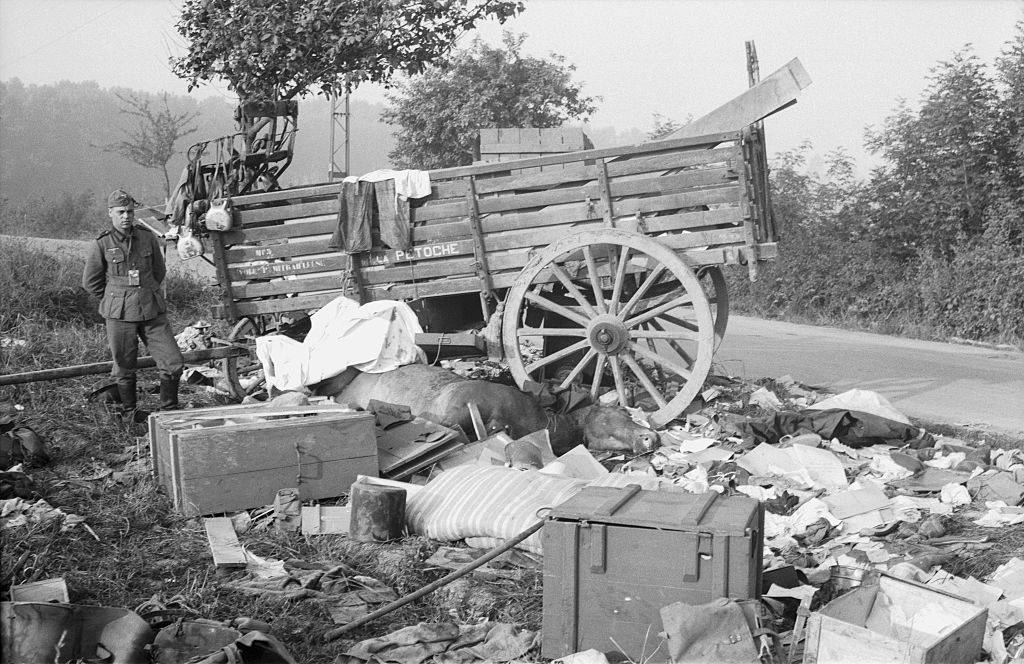 German soldier standing next to a ransacked cart