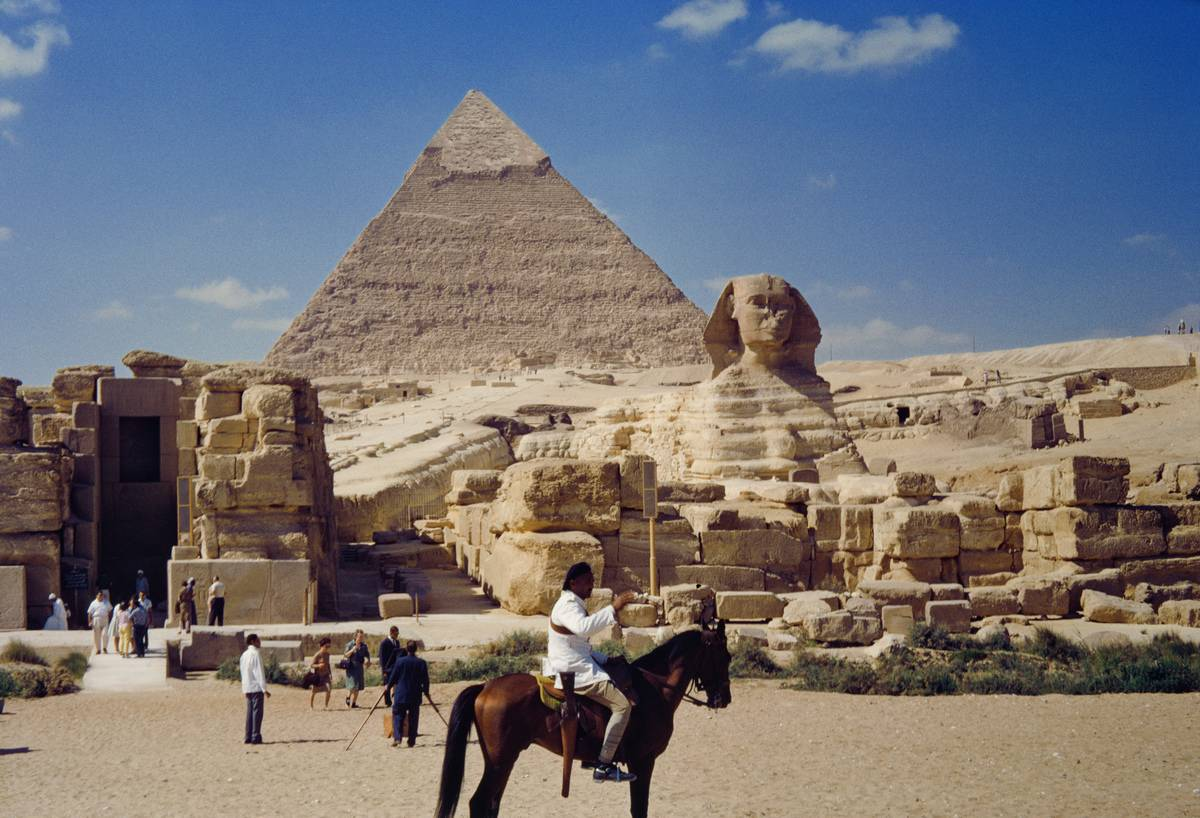 People on horseback are seen in front of a pyramid and the Sphinx.