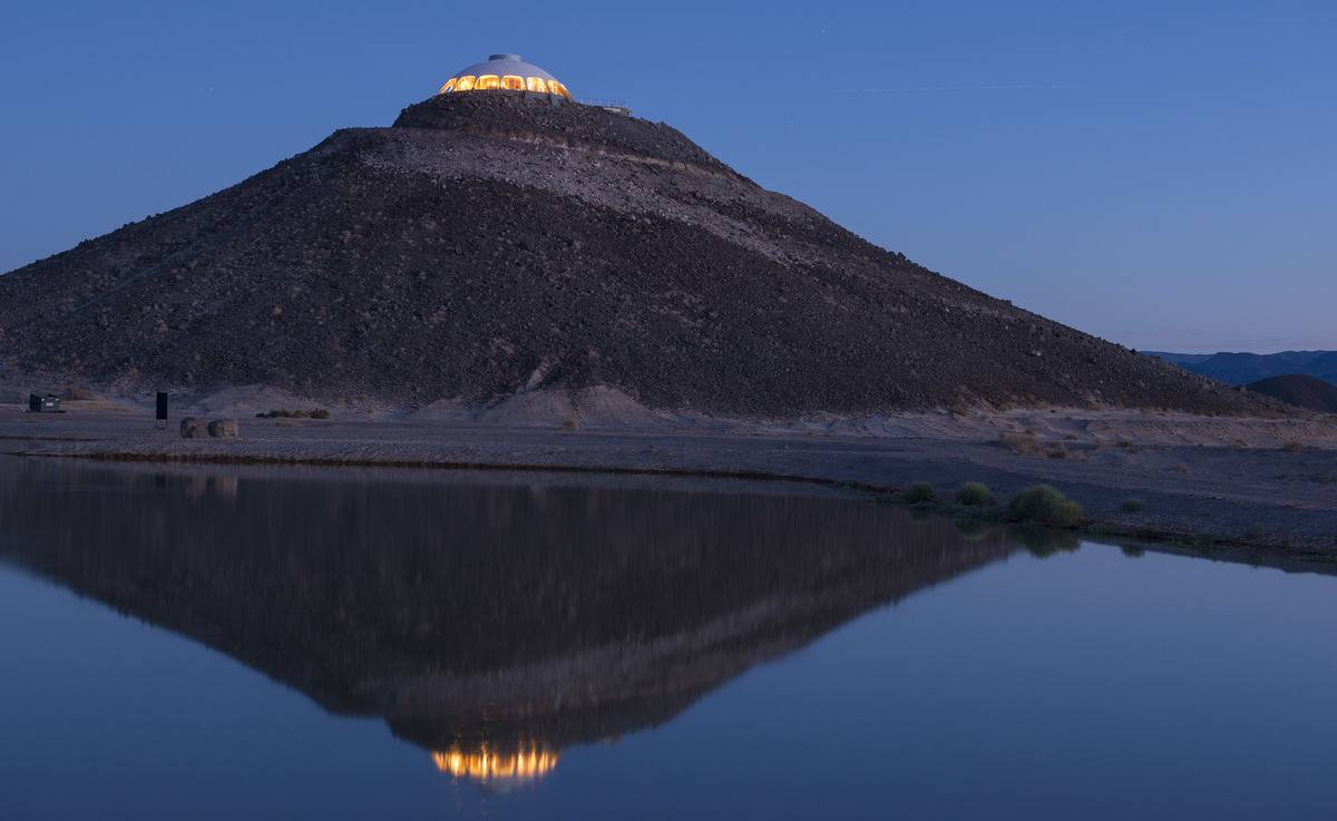 California's volcano house lights up at night on top of a hill.