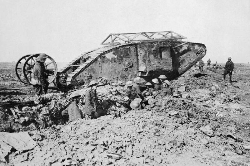 a tank from world war i with soldiers in a ditch