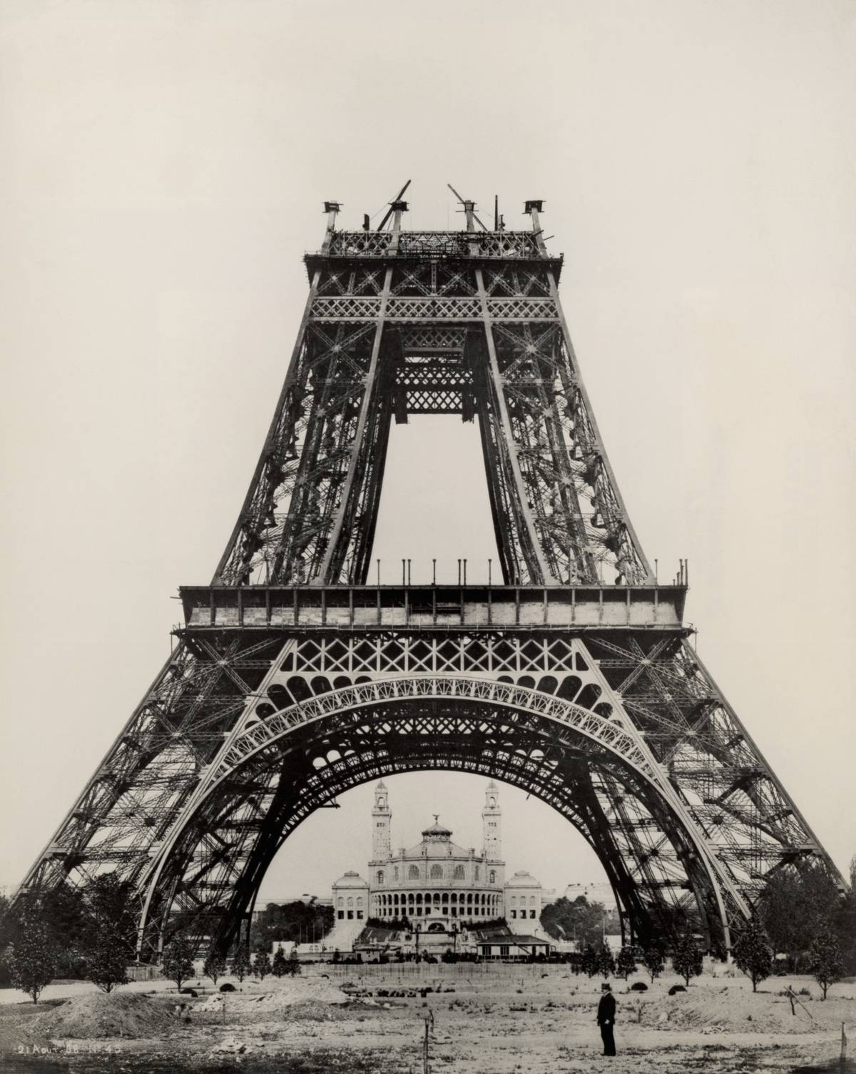Gustave Eiffel stands at the base of the Eiffel Tower while it is under construction.