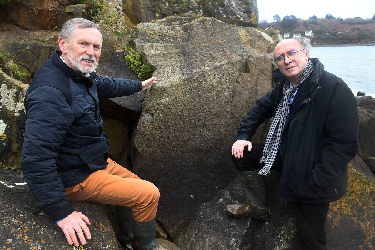 Frenchmen Robert Faligot (R) and Noel Rene Toudic pose near the inscripted rock they unscrambled