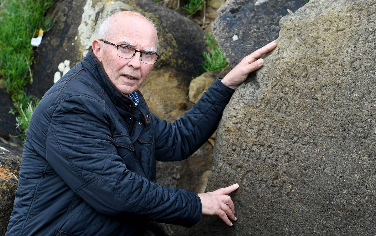 Michel Paugam motions toward inscriptions of the boulder.