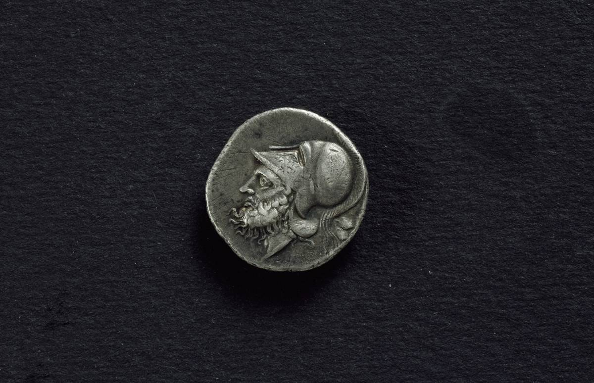 A Roman coin from 320 BC is laid on a black cloth.