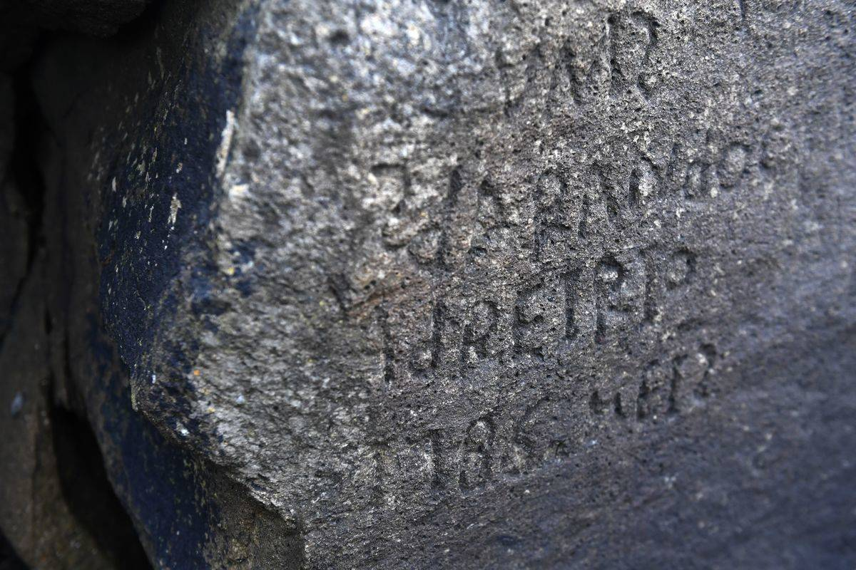 A close-up shows the inscriptions on the rock.