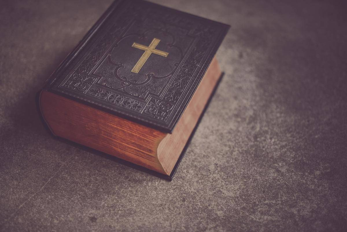 A Bible with a cross on it lies on a table.
