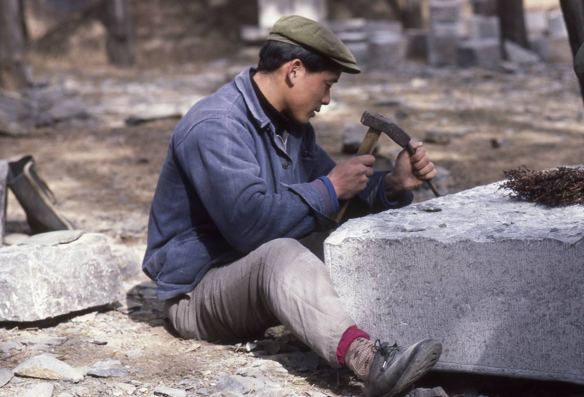 A Chinese man carves into stone, 1984.