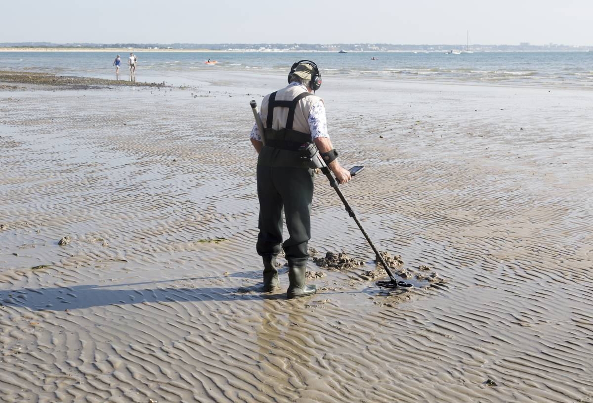 An elderly man searches the beach with his metal detector.