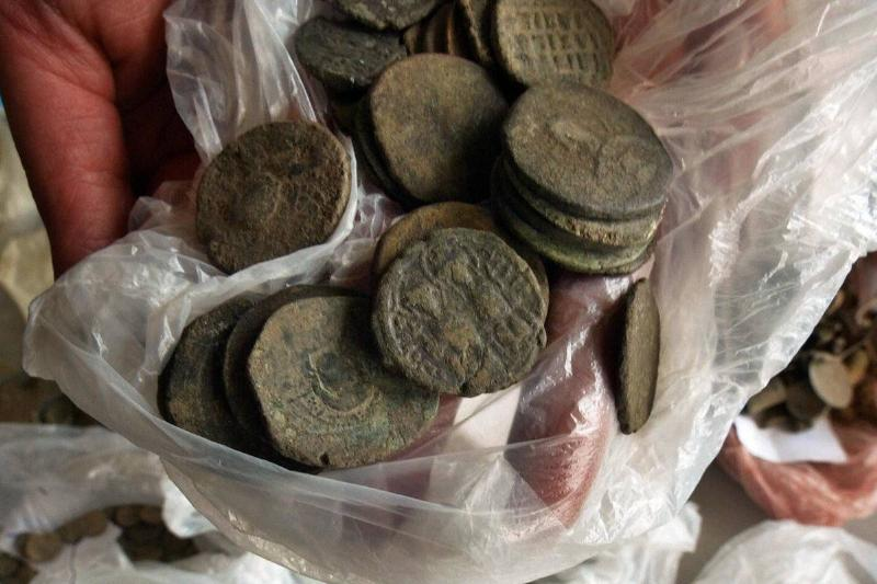 An archaeologist reveals plastic bags filled with Roman coins.