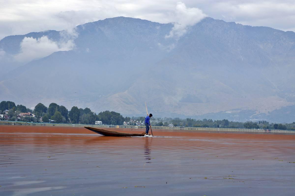 A boat man rows across a lake that has a red algae bloom.