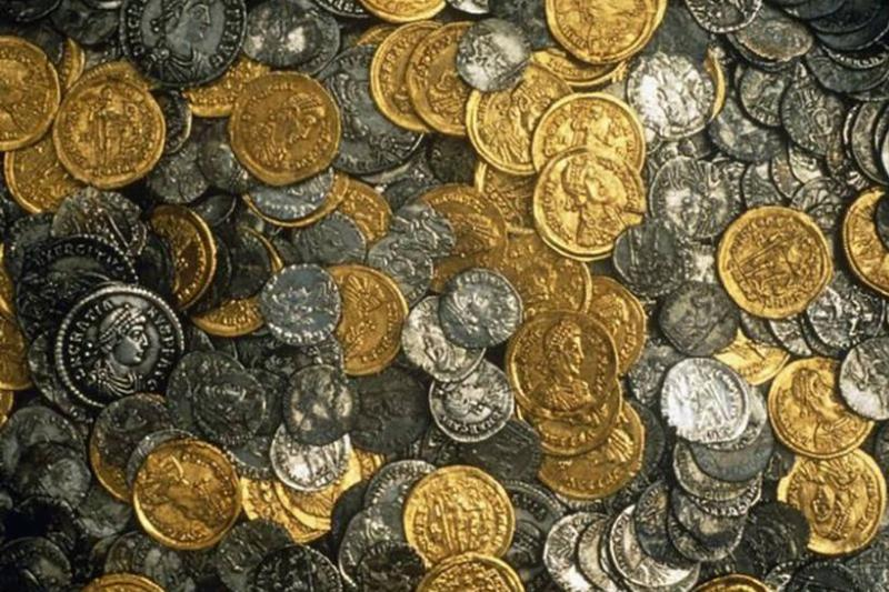 Silver and gold coins lie in a pile.