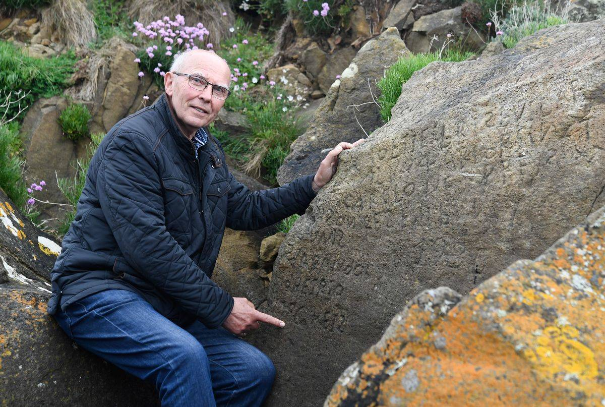 French local councillor in charge of small heritage Michel Paugam shows inscriptions composing indecipherable words on a rock.
