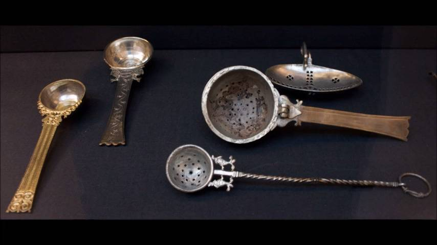 Spoons and strainers from the Hoxne Hoard are arranged on a table.